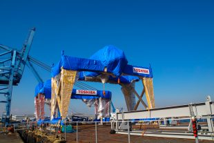 FHM (foreground) and crane are loaded onto a vessel at the port (photo provided by Toshiba Corporation).