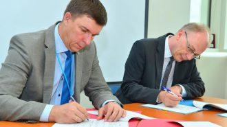 ウィーンで協定に署名するUMPの販売担当重役(=左)とIAEAのプロジェクト担当官©IAEA