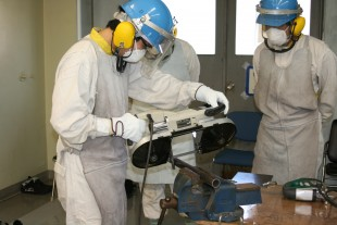 Wearing suitable garments, trainees handle tools in decommissioning training (JAEA).