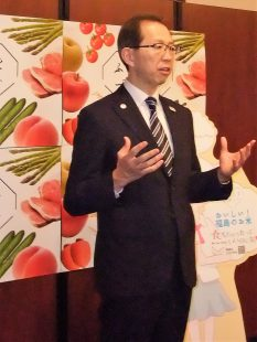 "Governor Uchibori tells the press, ""Eat and smile,"" in an effort to promote the attraction of Fukushima foods."
